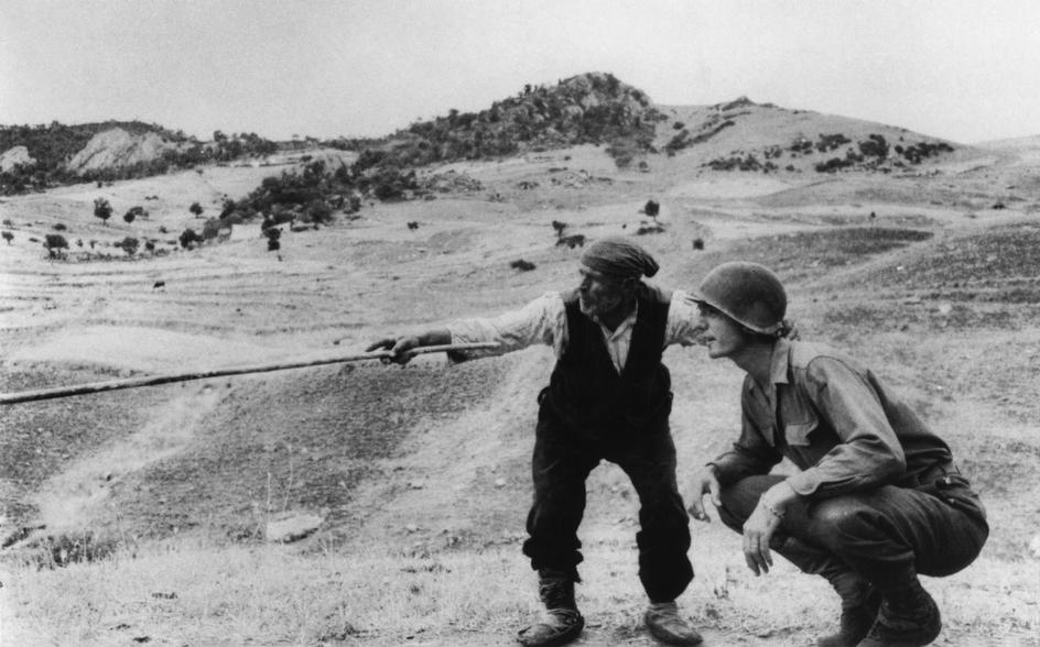 Campesino siciliano le cuenta a un soldado americano hacia dónde han ido los alemanes, por Robert Capa.