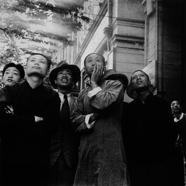 Población china observando la batalla entre bombarderos japoneses y aviones de combate chinos. Robert Capa, 1938.